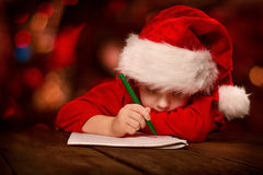 Christmas child writing letter in red Santa hat