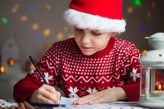 Christmas child writing letter to Santa Claus letter in red hat Stock Photos