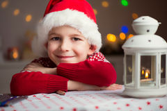 Christmas child writing letter to Santa in red hat Royalty Free Stock Images