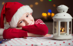 Christmas child writing letter to Santa in red hat Royalty Free Stock Photos