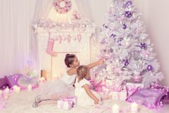 Christmas Children Decorating Xmas Tree, Kid and Baby Girls. In Holiday Decorated Family Home stock image