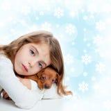 Christmas children girl hug a puppy brown dog. Christmas snowflakes with children girl hugging a puppy brown dog stock photo