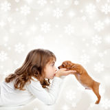 Christmas children girl hug a puppy brown dog. Christmas snowflakes with children girl hugging a puppy brown dog stock images