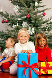 Christmas - Children with presents. Family Christmas - three children having received gifts showing them around Stock Images