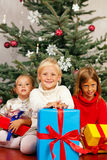 Christmas - Children with presents. Family Christmas - three children having received gifts showing them around Royalty Free Stock Photo