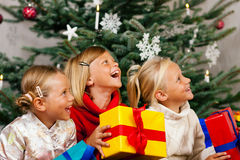 Christmas - Children with presents. Family Christmas - three children having received gifts showing them around Royalty Free Stock Images