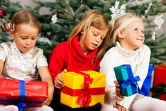 Christmas - Children with presents. Family Christmas - three children having received gifts showing them around Royalty Free Stock Image
