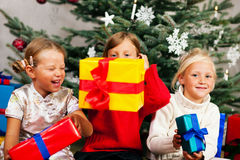 Christmas - Children with presents. Family Christmas - three children having received gifts showing them around Royalty Free Stock Photography