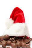 Christmas chocolate. Pieces of milk chocolate and santa hat  on a white background Royalty Free Stock Photos