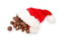 Christmas chocolate. Pieces of milk chocolate and santa hat  on a white background Stock Image