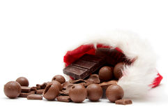 Christmas chocolate. Pieces of milk chocolate and santa hat  on a white background Royalty Free Stock Image