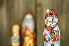 Christmas chocolate figures in a wrapper. On wooden background Royalty Free Stock Photo