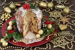Christmas Chocolate Panettone Cake. With gold bauble decorations, holly, mistletoe, ivy, fir, pine cones on oak table background Royalty Free Stock Image