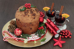 Christmas Chocolate Panettone Cake. With mulled wine, bauble decorations, candy canes, holly, mistletoe, fir, gold pine cones on oak background Stock Photo