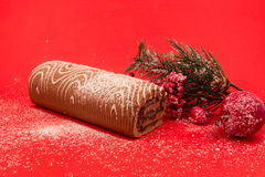 Christmas chocolate Swiss roll cake isolated on red background Royalty Free Stock Image