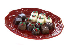 Christmas chocolate truffles. Christmas decorated chocolate truffles on a red plate royalty free stock photography