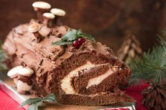 Christmas chocolate yule log with decor of colored chocolate on a wooden table. Stock Images