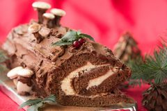 Christmas chocolate yule log with decor of colored chocolate on a wooden table. Royalty Free Stock Photos