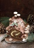 Christmas chocolate yule log with decor of colored chocolate on a wooden table. Stock Photos