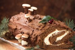 Christmas chocolate yule log with decor of colored chocolate on a wooden table. Royalty Free Stock Images
