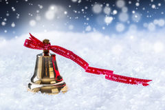 Christmas. Christmas bell with red ribbon and snowy background. Happy christmas text Royalty Free Stock Image