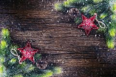 Christmas. Christmas fir tree with star and  pine cone on rustic wooden table. Diagonally composition border in snowy atmosphere Royalty Free Stock Images