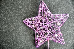 Christmas. Purople star on black background .With copy-space Royalty Free Stock Photography