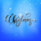 Christmas. Christmas script lettering on the snow winter background. Winter holiday card with snowflakes and calligraphy.  Stock Photography