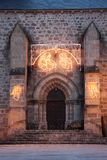 Christmas Church Nativity Lights. The entrance to an old stone church adorned with shining Christmas lights of the Nativity and angels, vertical Stock Image