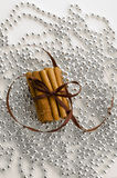 Christmas cinnamon. Cinnamon sticks tied with brown ribbon on a background of silver beads Royalty Free Stock Images