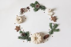 Christmas circle floral composition. Wreath of fir tree branches, pine cones, confetti, wooden stars, white pumkins on