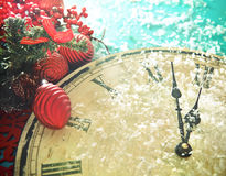 Christmas clock and fir branches covered with snow Stock Photos