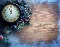 Christmas clock over snow wooden background. Royalty Free Stock Photos