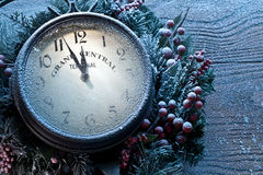 Christmas clock over snow wooden background. Royalty Free Stock Photography