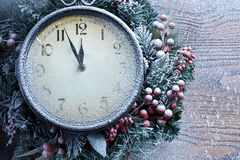 Christmas clock over snow wooden background. Royalty Free Stock Image
