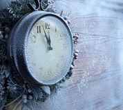 Christmas clock over snow wooden background. Royalty Free Stock Photo
