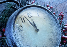 Christmas clock over snow wooden background. Royalty Free Stock Images