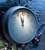 Christmas clock over snow wooden background. Stock Image