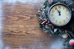 Christmas clock over snow wooden background. Stock Photos