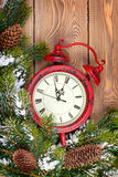 Christmas clock over wooden background with snow fir tree Royalty Free Stock Photos