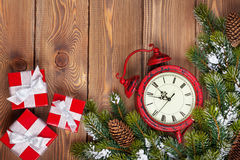 Christmas clock over wooden background with snow fir tree and gi Royalty Free Stock Photos