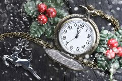 Christmas clock with winter decoration on snow. Happy new year concept royalty free stock photo