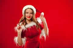 Christmas Close up portrait of beautiful girl wearing santa claus clothes, over red background Stock Photos