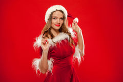 Christmas Close up portrait of beautiful girl wearing santa claus clothes, over red background Royalty Free Stock Photography