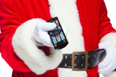 Christmas. Close-up. Santa Claus in white gloves holding the TV remote control. Browse Christmas TV listings, select the. Channel. on white background Stock Images