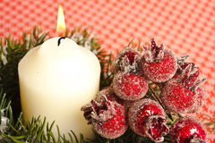 Christmas. Close-up to Christmas candle and red rose hip stock photography