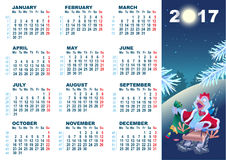 Christmas cock rolls on sledge from mountain. Blue cartoon Rooster symbol 2017 and wall calendar Royalty Free Stock Photo