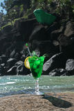 Christmas Cocktail. Green Christmas cocktail on a rock at the beach, with the ice dropped in it with all the fluid splashing out royalty free stock photo