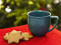 Christmas coffe and ginger bread cookies. Christmas coffee and star shaped ginger bread cookies with christmas tree in background royalty free stock image