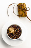 Christmas coffee beans and cinnamon. Cup with coffee beans and a gingerbread man and cinnamon sticks tied with brown ribbon Royalty Free Stock Photo